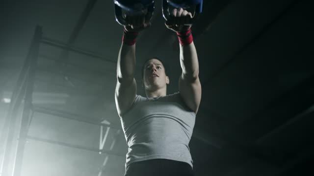focused man doing exercise with kettlebell at gym - giria filmów i materiałów b-roll