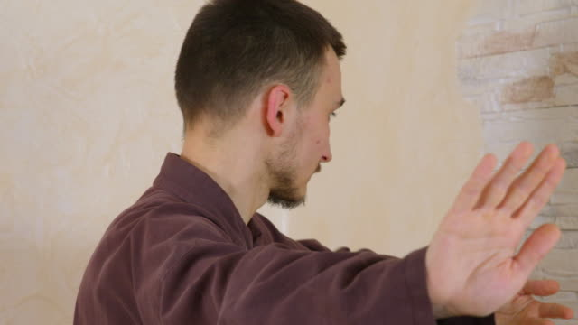Focused man practicing tai chi exercise repulse monkey on stony wall background. Concentrated man training traditional qigong martial gymnastics.