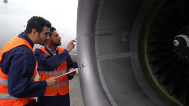 Focused men checking the airplane's turbine while checking off a list on clipboard Focused men checking the airplane's turbine while checking off a list on clipboard both very serious turbine stock videos & royalty-free footage