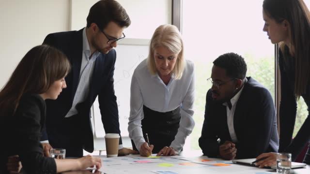 vídeos de stock e filmes b-roll de focused middle aged female team leader analyzing paper reports. - envolvimento dos funcionários