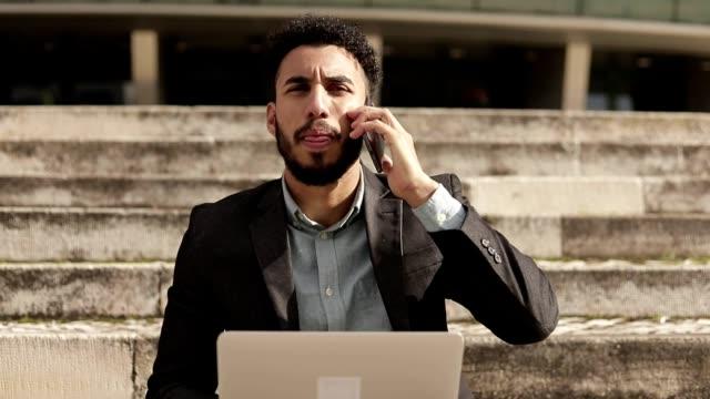 uomo d'affari mediorientale concentrato che lavora all'aperto. - cultura del medio oriente video stock e b–roll