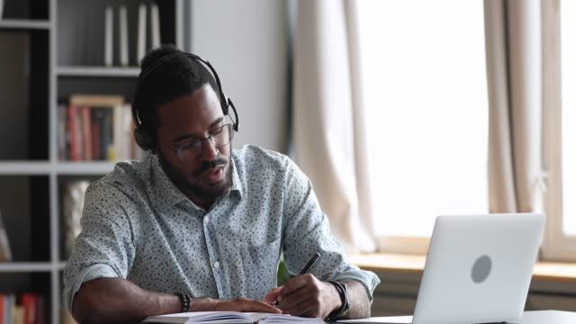 fokussierte millennial gemischte rasse männlichen studenten, die pädagogische vorlesung online. - dozenten stock-videos und b-roll-filmmaterial
