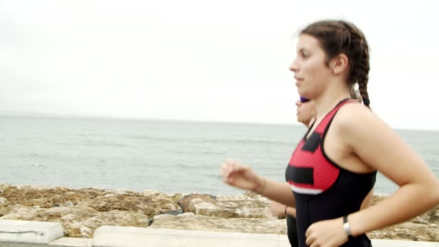 Focused positive female athletes training for marathon Focused positive female athletes training for marathon at seaside promenade together. Women in sportswear running outdoors. Medium shot, tracking, dolly. Sport concept sideways glance stock videos & royalty-free footage