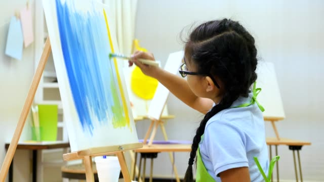 Focused preteen Asian girl paints in art class video