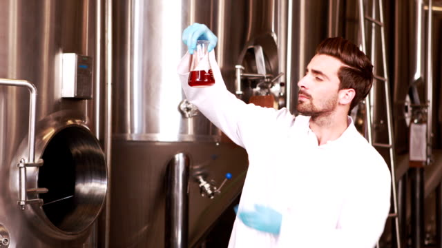 Concentrato scienziata guardando bicchiere con birra - video