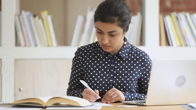 focalizzato smart indian girl college university student study in biblioteca - esame università video stock e b–roll