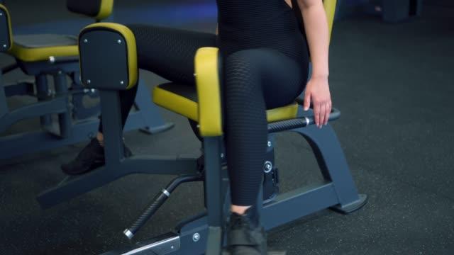 Focused sportswoman exercising at hip abductor machine video