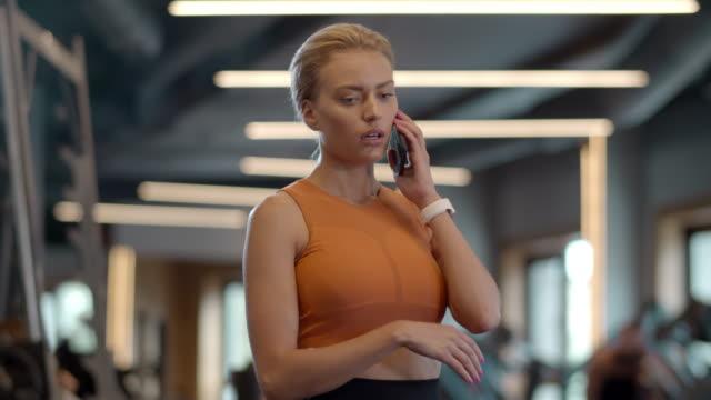 stockvideo's en b-roll-footage met geconcentreerde sportswoman die op telefoon bij gymnastiek spreekt. het meisje dat van de atleet zich in sportclub bevindt - call center