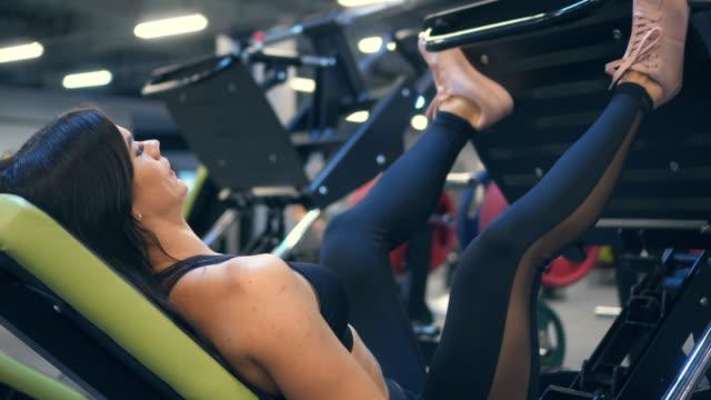 vídeos de stock e filmes b-roll de focused sportswoman working out on leg press machine - aparelho de musculação
