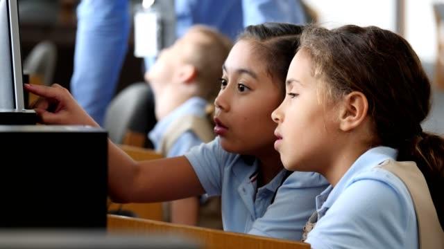 сосредоточенные stem элементарные школьницы изучают что-то на компьютере в компьютерной лаборатории - филиппинского происхождения стоковые видео и кадры b-roll