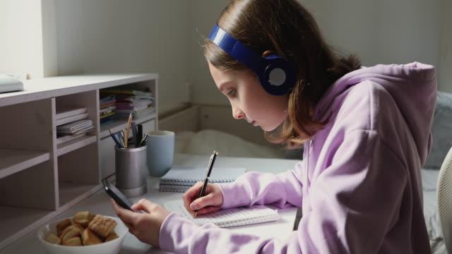 Focused teenage girl wearing headphones using mobile education app