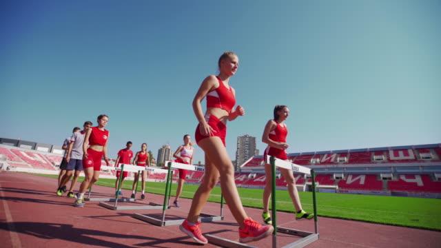 vídeos y material grabado en eventos de stock de corredores adolescentes concentrados hurdling - valla artículos deportivos
