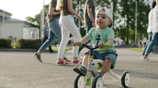 Focused toddler in amusement park. Little kid making first try on bike outside