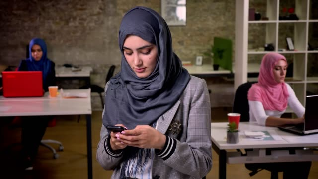 focused typing arabic female is using her smartphone while standing in her grey nice hijab in front of other working females indoor - abbigliamento modesto video stock e b–roll