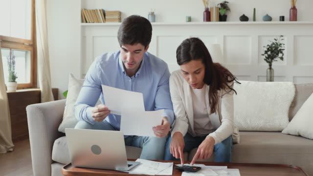 fokuserad kvinna hjälpa man planerar investeringar tillsammans hemma. - stavning bildbanksvideor och videomaterial från bakom kulisserna
