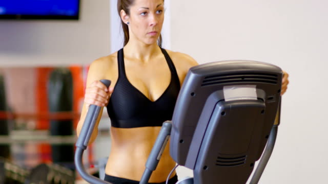 Focused woman training on ellipse exercise machine in fitness gym video