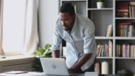 istock Focused young african man working from home standing at table. 1220336270