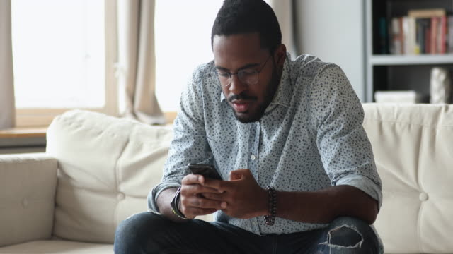 Focused young biracial guy using mobile apps on phone.