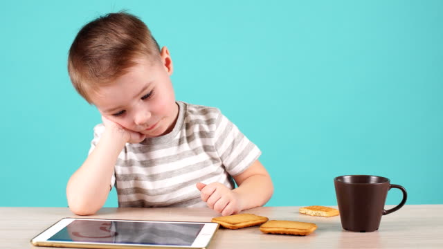 focused young boy uses tablet to learn new programs - solo neonati maschi video stock e b–roll