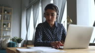 istock Focused young indian student wearing wireless headphones, studying online. 1214995882