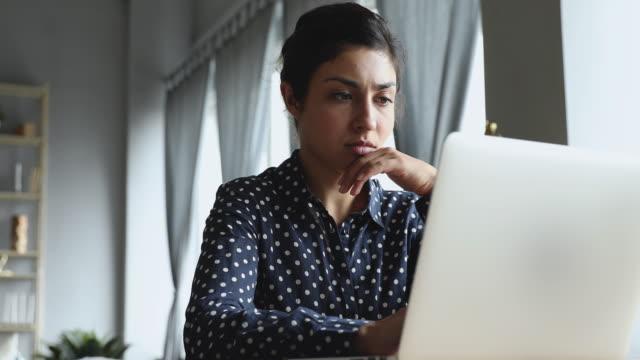 сосредоточенная молодая индийская женщина смотрит на монитор компьютера. - дистанционный стоковые видео и кадры b-roll