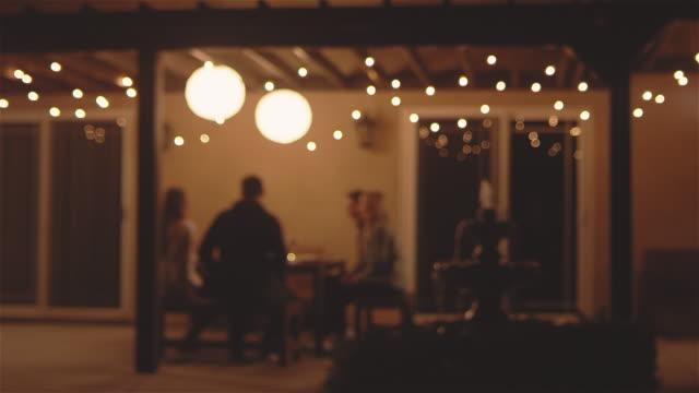テラス テーブルで夕食を食べていくつかの若い人たちの撮影中心に広い - パティオ点の映像素材/bロール