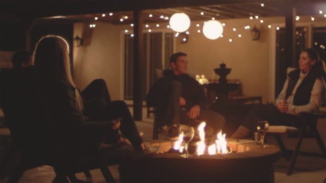 広いパティオ火災で座っている若い魅力的な人々 の撮影を中心 - パティオ点の映像素材/bロール