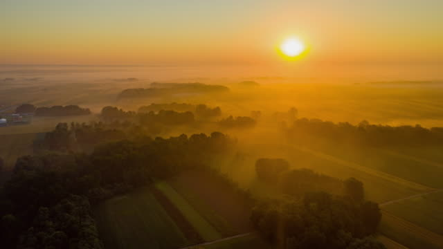 H/L Fog floating over cultivated fields Hyper lapse drone shot of a fog floating over a dirt road among cultivated fields in the countryside. clear sky stock videos & royalty-free footage