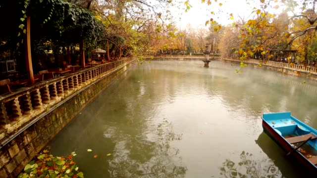 Fog Floats under Lake Ayn-Zelih Blue Boat on Water near Restaurant around Green and Yellow Trees Park Urfa video
