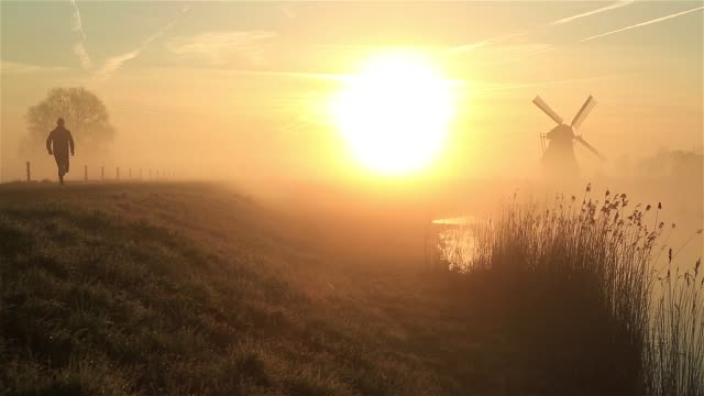 Fog run Man running during a foggy, spring sunrise in the Dutch countryside. april stock videos & royalty-free footage