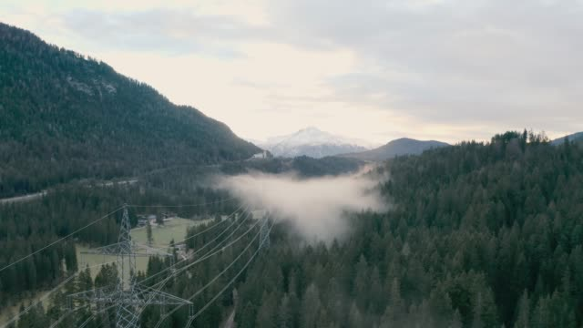 Foggy Forest in Mountains Forested mountain slope in low lying cloud with the evergreen conifers shrouded in mist in a scenic landscape view high voltage sign stock videos & royalty-free footage
