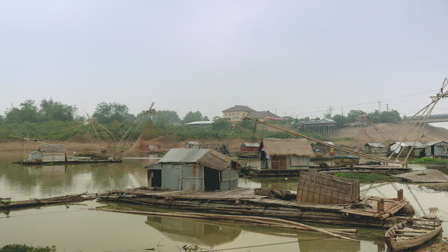 Foggy river landscapes with houseboats and Chinese fishing nets