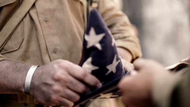 Folding American Flag American World War 2 soldier folding American flag at war memorial service. armed forces stock videos & royalty-free footage