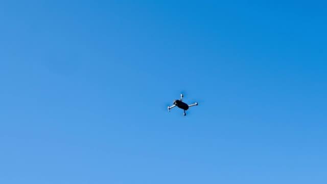 vídeos de stock e filmes b-roll de folding drone flying at the blue sky - multicóptero