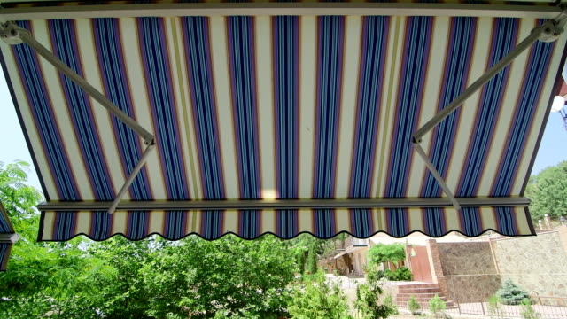Folding retractable awning mounted onto the outside wall of house video