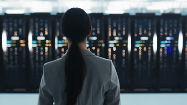 vídeos de stock e filmes b-roll de follow back shot of a female it chief engineer in a jacket walking towards a server rack in data center room. - tecnologia