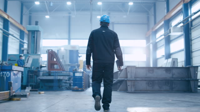 follow footage of factory worker in a hard hat that is walking through industrial facilities. - acciaio video stock e b–roll