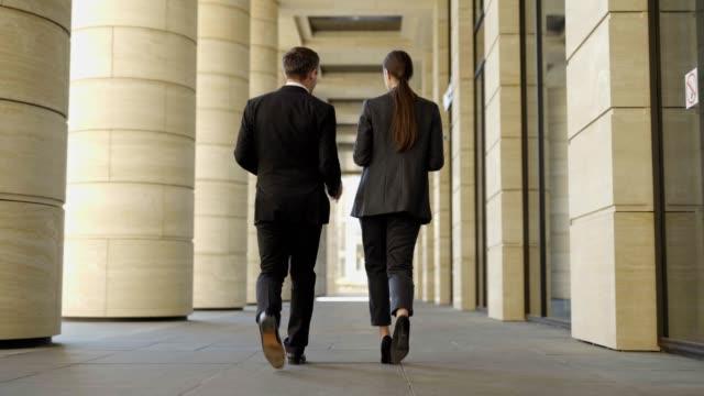 フォーマルなスーツを着た中年の男女が一緒に通りを歩き、話をしている2人のビジネスプロフェッショナルの完全な長さのバックビューに従ってください。自分の意見を説明しながら身振り - 全身点の映像素材/bロール