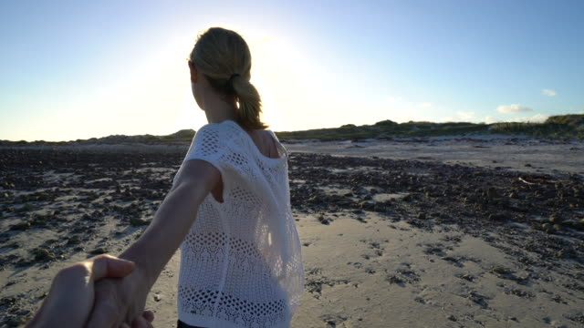 Follow me concept-Young woman leading boyfriend to the beach video