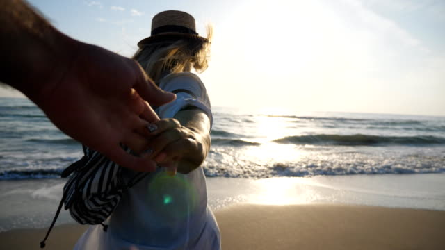 vídeos de stock, filmes e b-roll de siga-me tiro de mulher com mochila levando o namorado na costa do mar ao pôr do sol. menina no beachwear que libera a mão masculina e que funciona ao oceano que mostra emoções alegres. conceito de férias de verão. pov - férias na praia