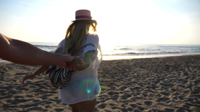 vídeos de stock e filmes b-roll de follow me shot of young woman in shirt with backpack pull her boyfriend to the sea coast. happy couple spending time together outdoor. summer holiday or vacation concept. slow motion pov - mochila saco