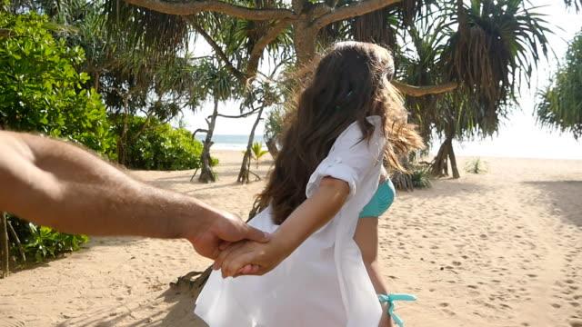 海岸に彼氏若い女性プルのショットを私に従ってください。男性の手を握って、熱帯のエキゾチックなビーチに海を実行する少女。夏休みや休日。ビューのポイント。povスローモーション - 異国情緒点の映像素材/bロール