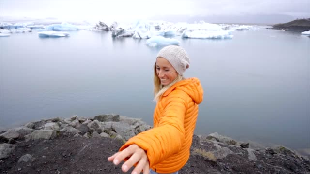 Follow me to concept, young woman leading boyfriend to glacier lagoon in Iceland video