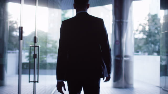 follow shot of businessman walking on streets of business district. - business suit stock videos & royalty-free footage