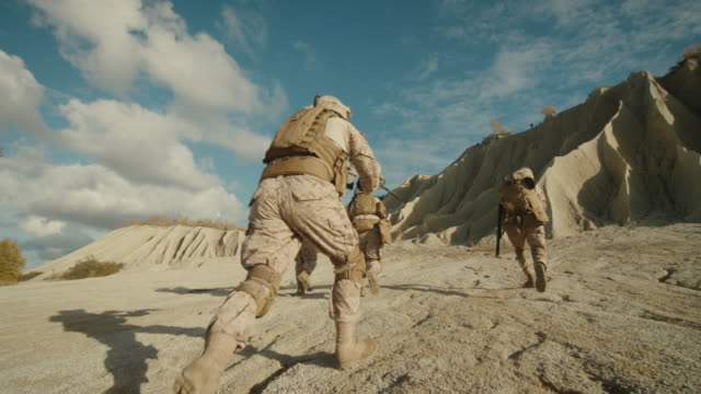 Follow Shot of Squad of Soldiers Running Forward During Military Operation in the Desert. Slow motion. - vídeo