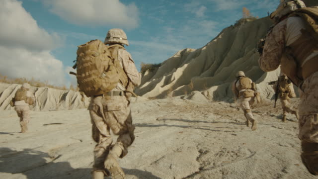 Follow Shot of Squad of Soldiers Running Forward During Military Operation in the Desert. video