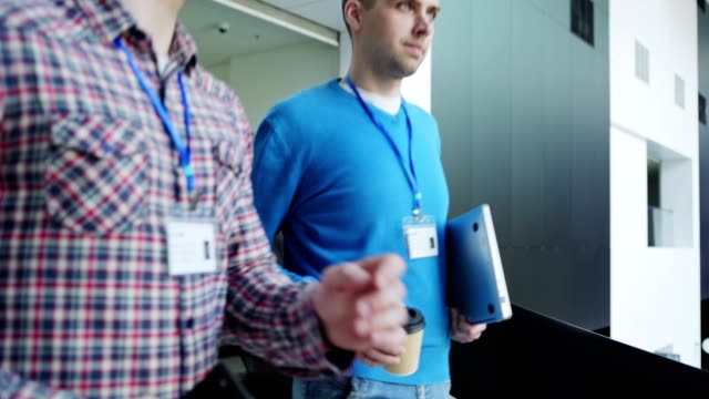 follow shot of two young business event attendees walking down stairs after conference in modern business center and talking. men holding laptop computer; takeaway coffee cup and cell phone - badge video stock e b–roll