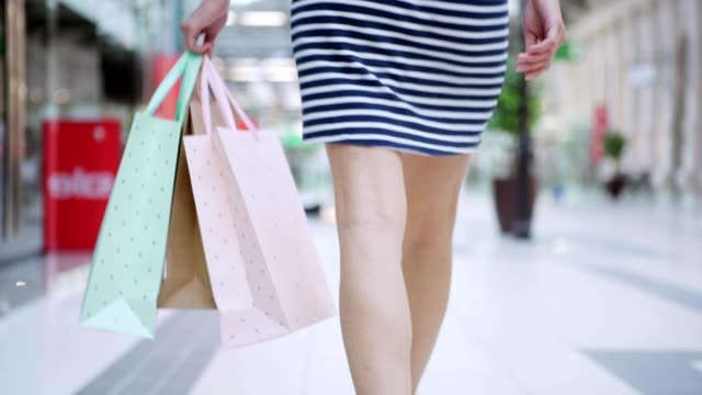 vídeos de stock e filmes b-roll de follow shot of unrecognizable young woman in striped dress leaving shopping mall with paper bags in her hand - tote bag