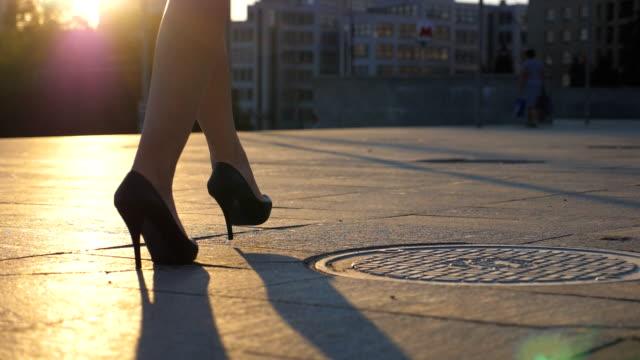vídeos de stock, filmes e b-roll de siga para as pernas femininas em sapatos de salto alto andando ao longo da rua da cidade no tempo do por do sol. pés da mulher de negócio no calçado high-heeled que vai na cidade. menina que pisa ao trabalho. fim do movimento lento acima - salto alto