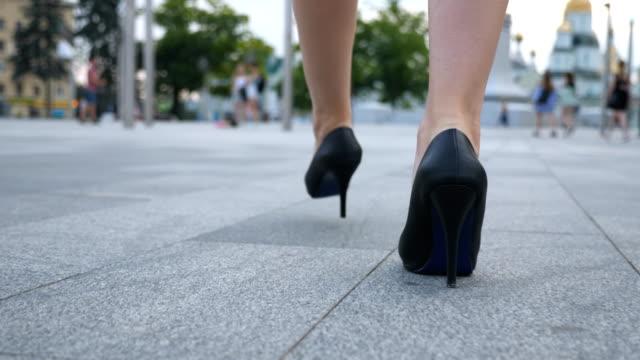 女性ハイヒールの靴が都市通りの歩行で足に従ってください。都市はかかとの高い靴の若いビジネス女性の足。ステップ動作する認識できない女の子。スローモーションのすぐ後方を背面図 - 靴点の映像素材/bロール